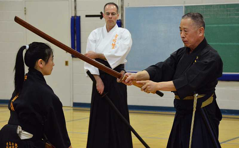 by: REVIEW, TIDINGS PHOTOS: VERN UYETAKE - Grand master samurai swordsman Sekiguchi Komei demontrates a move to pupil Sonoko Beers as her husband, Chad Beers, observes in the background.
