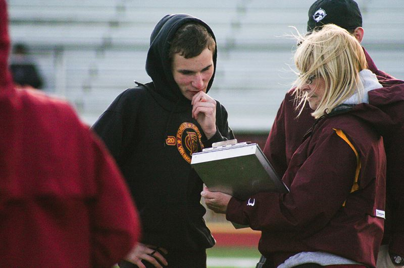 by: NEWS-TIMES PHOTO: AMANDA MILES - Forest Grove junior Geremia Lizier-Zmudzinski, who won a state title in the 1,500 meters last spring, chats with distance coach Sue Fleskes at last Wednesday's dual meet against McMinnville.