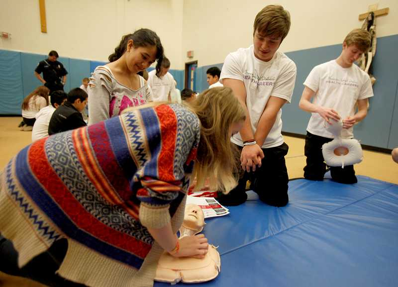 by: TIMES PHOTO: JONATHAN HOUSE - Beaverton Health Careers mentor Mark Iguidbashian, center, teaches Ashlynn Christensen proper hands-free CPR technique during a Whitford Middle School assembly.