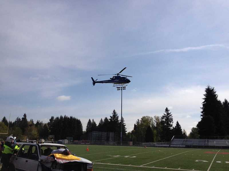 by: COURTESY OF TVF&R - Captain Mark Daniel ensures that Life Flight has enough room to land on the athletic film during a simulated fatal accident at Sherwood High School Wednesday.