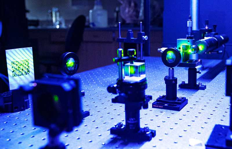 by: PAMPLIN MEDIA GROUP: JOSH KULLA - A green laser, which typically uses helium to obtain its color, is shown in the optics laboratory at Oregon Tech's Wilsonville campus.