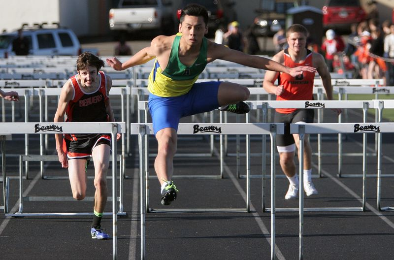 by: MILES VANCE - DOUBLE WINNER - Aloha's Edward Tran clears the last hurdle on his way to victory in the 110-meter high hurdles against Beaverton last week.