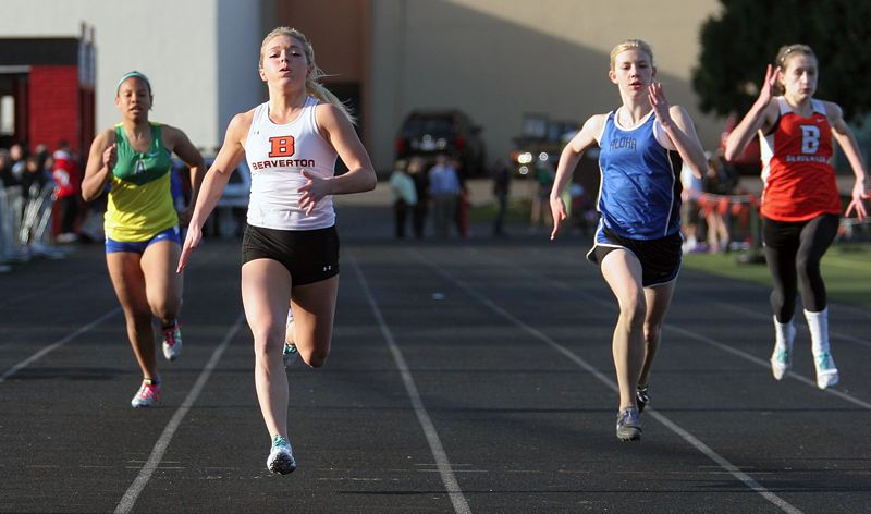 by: MILES VANCE - SPEED BURNER - Beaverton junior Molly Mutz-McCay (center) races to victory in the 200-meter dash against Aloha last week at Beaverton High School.