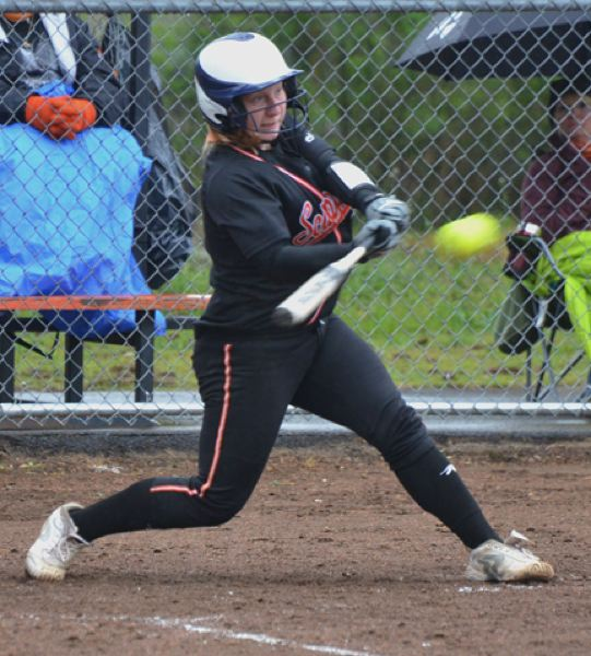 by: JOHN BREWINGTON - Home run swing. Scappoose's Lexi Courtney smashed this ball over the fence for one of Scappoose's two runs against Banks.