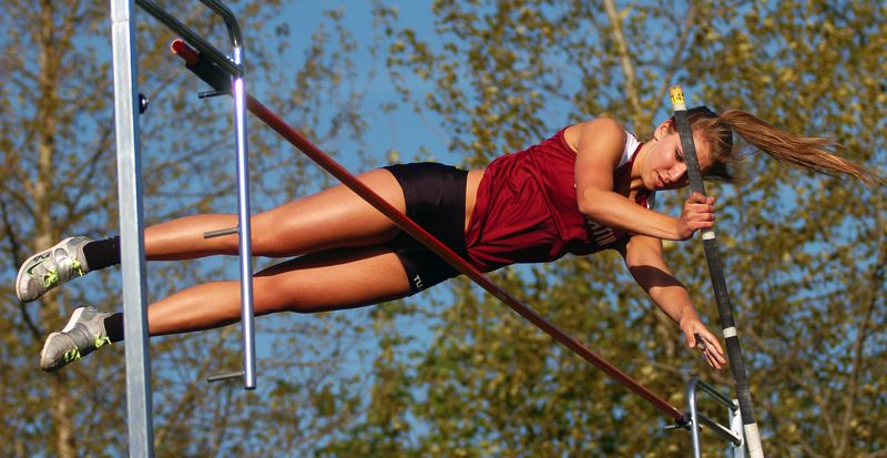 by: DAN BROOD - UP AND OVER -- Tualatin High School junior Laura Taylor clears a school-record height of 11 feet, 6 inches during last week's dual meet at Tigard High School. Tigard junior Liz Prouty cleared 11-0 at the meet.