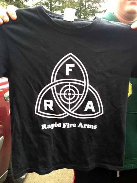 by: CONTRIBUTED PHOTO - This is an example of the T-shirt design worn by members of the Sandy Cal Ripkin League T-ball team sponsored by Rapid Fire Arms.