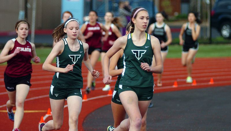 by: DAN BROOD - STRIDING OUT -- Tigard High School junior Megan Franz (right) with teammates Elizabeth Dean and Hannaly Duff-McGaughey right behind her, is on her way to victory in the 1,500-meter run during last week's Pacific Conference dual meet with Tualatin.