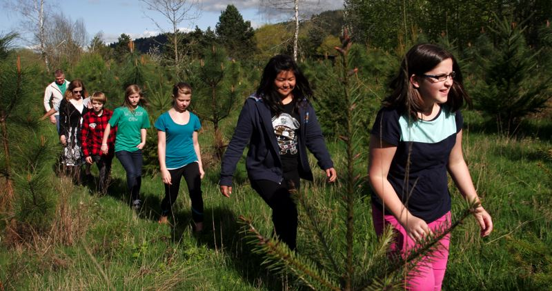 by: OUTLOOK PHOTO: JIM CLARK - Students from Pleasant Valley Elementary School lead the way to their personal trees in the school´s 10-acre greenspace.