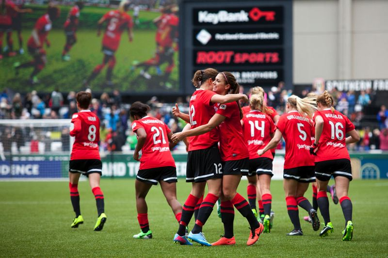 by: TRIBUNE PHOTO: CHRISTOPHER ONSTOTT - Alex Morgan gets a hug from Christine Sinclair (12) after the two combined on Portland's second goal (Morgan scoring, Sinclair assisting) Sunday at Jeld-Wen Field, where the Thorns beat Seattle Reign FC 2-1 in their home opener.