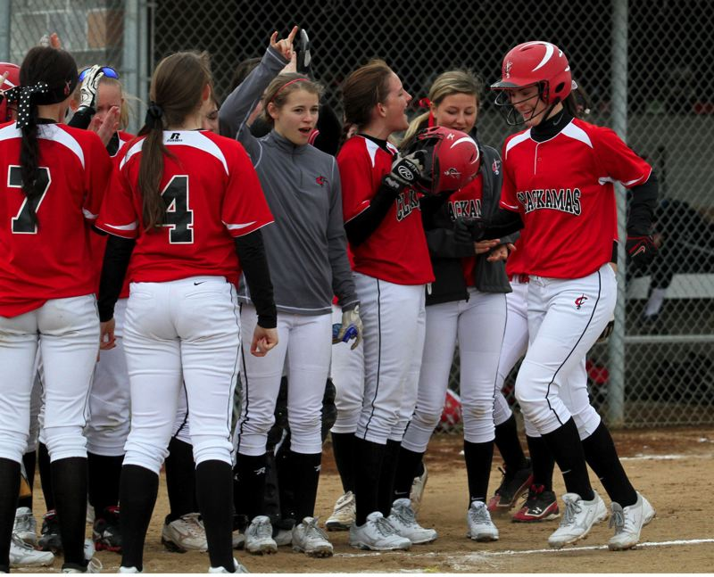 by: JONATHAN HOUSE - Clackamas' Cassie Haehlen is greeted by her teammates after hitting a home run in the second inning of last Fridays 12-0 rout of Lake Oswego.