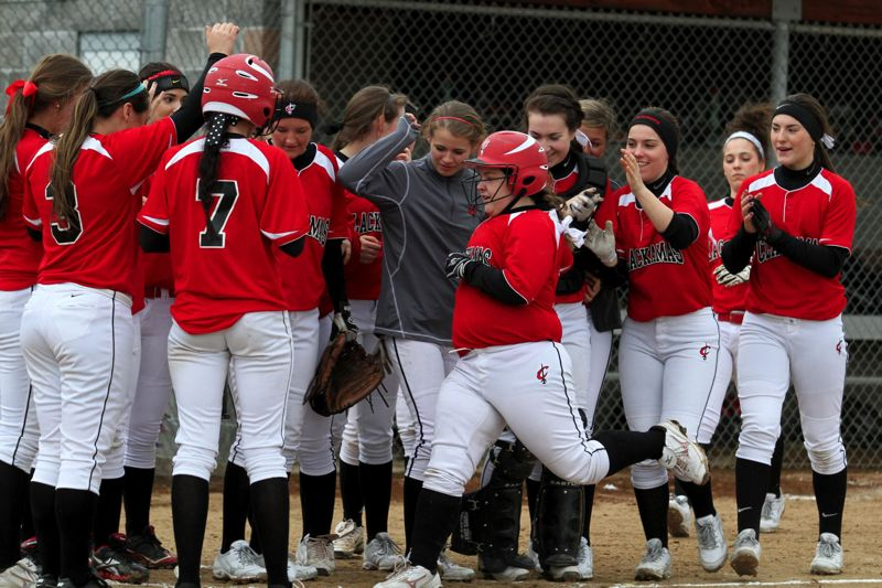 by: JONATHAN HOUSE - Clackamas' Jessica Engle is greeted by her teammates after hitting a home run in last Fridays 12-0 rout of Lake Oswego. It was Engle's first home run of her high school career.