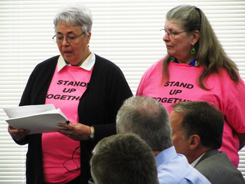 by: OUTLOOK PHOTO: LISA ANDERSON - Brenda Cook, a colleague of Principal Tom Klansnic, wore a 'Stand Up Together' T-shirt as she read a statement to the school board Thursday, April 18.