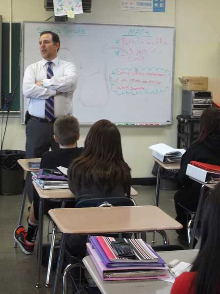 by: POST PHOTO: NEIL ZAWICKI - Cedar Ridge Middle School Principal Matt Newell explains to seventh graders Thursday how, if they do well enough on the state test, they can earn the right to give him a Mohawk.
