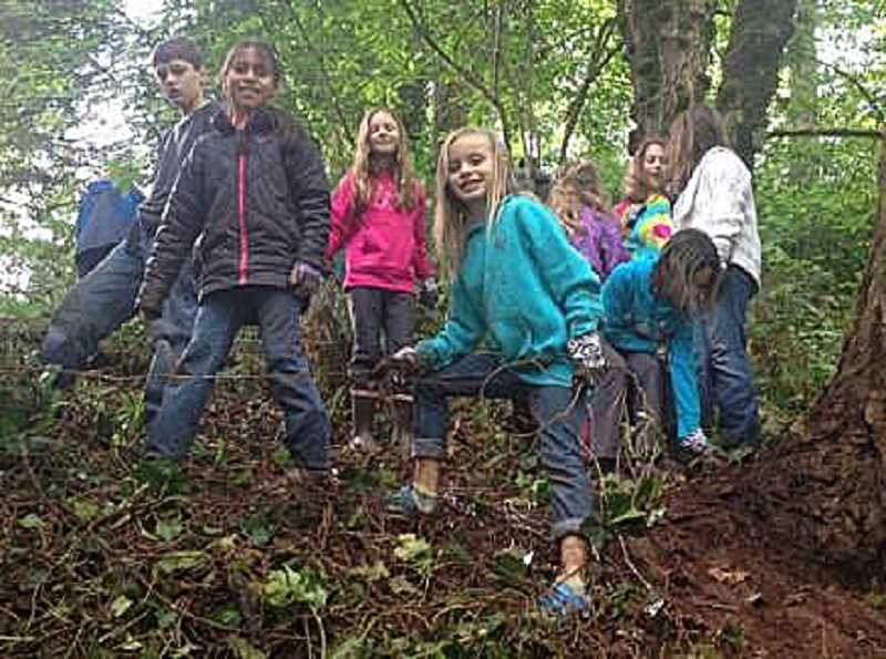 by: SUBMITTED PHOTO - From left, Aiden Brody, Victoria Garcia, Olivia McDonald, Noelle Herricks and Robin Brody work to pull up ivy at Maddax Woods to celebrate Olivia McDonald's ninth Earth Day birthday.