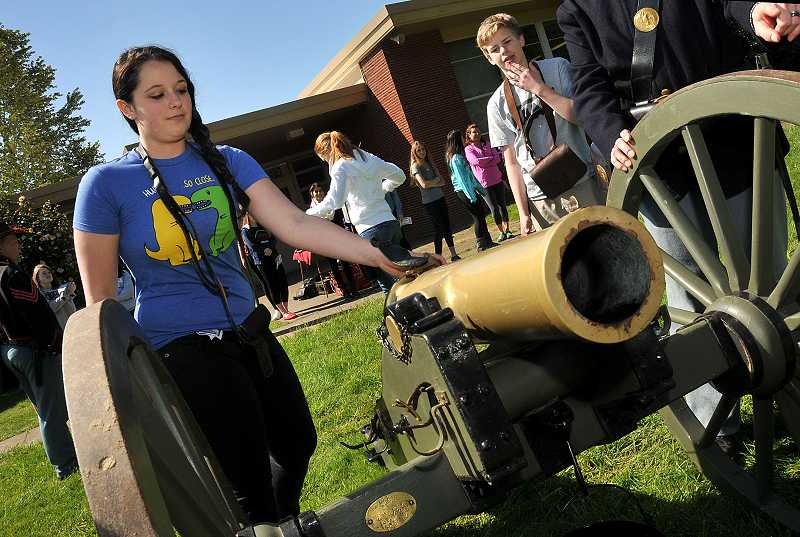 by: REVIEW PHOTO: VERN UYETAKE - Daylee Shaw helps prepare a cannon for firing.