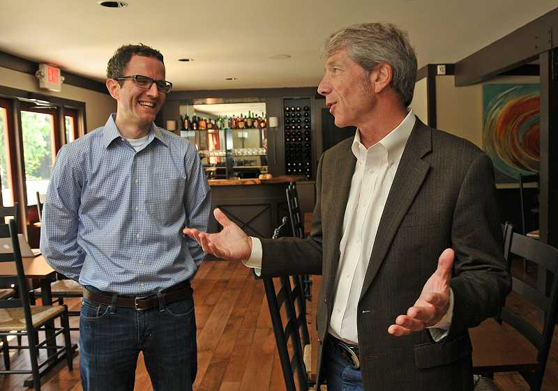 by: REVIEW PHOTO: VERN UYETAKE - Joe Buck, left, tells Congressman Kurt Schrader about the delicious hot waffles offered at Babica Hen in Lake Grove.