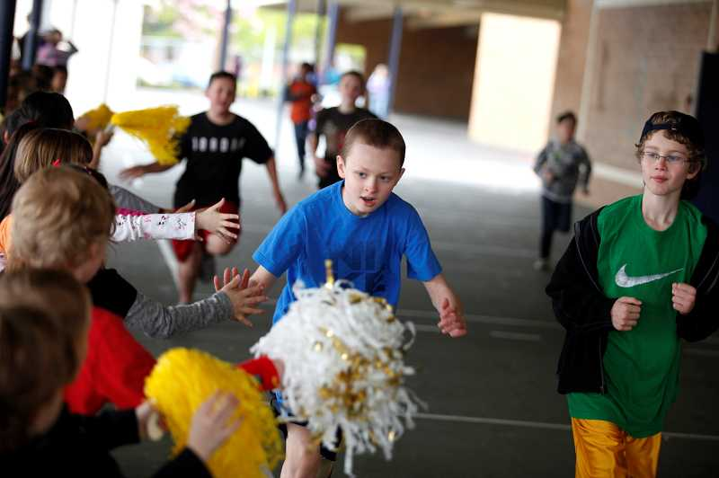 by: TIMES PHOTO: JONATHAN HOUSE - Sam Day gives out high-fives to fellow classmates as he runs through a Terra Linda Elementary breezeway as part of the annual 'SamRock Run.' The event is a charity drive that benefits the Challenge Athletes' Foundation.