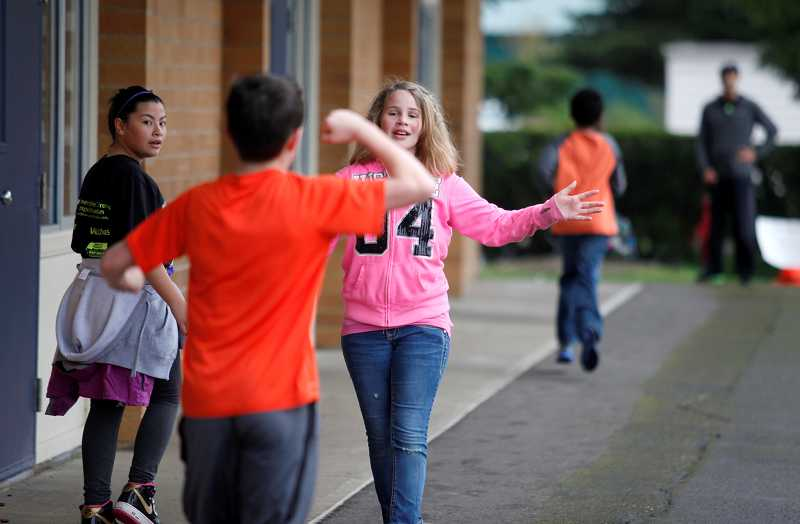 by: TIMES PHOTO: JONATHAN HOUSE - Brianna Gonser encourages a tired classmate during the SamRock Run at Terra Linda Elementary School on Friday.