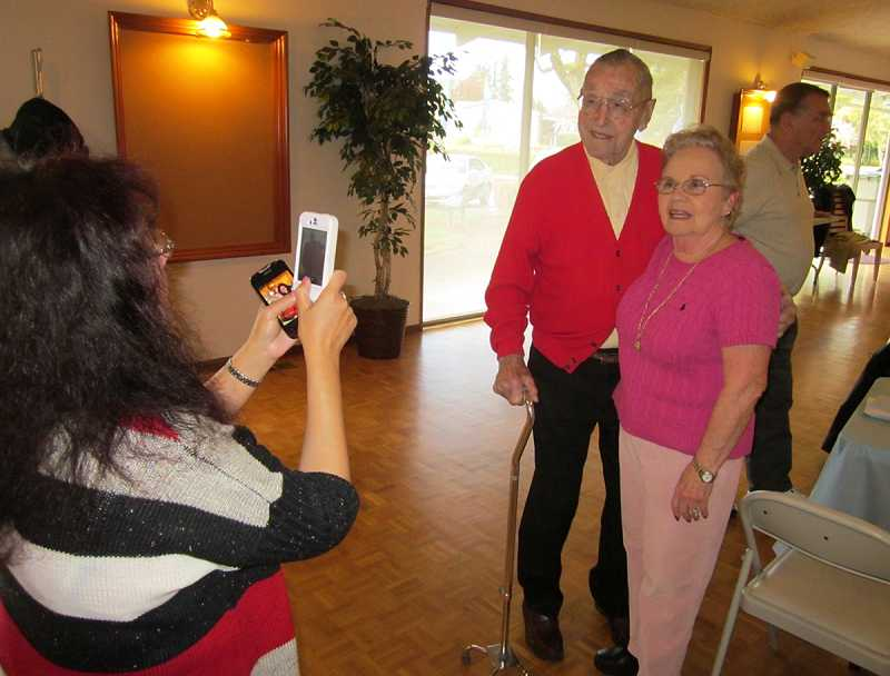 by: BARBARA SHERMAN - HE'S 104 AND COUNTING - Linda Estrada takes a photo of Curt Tigard with Gilda Burks at his birthday breakfast at the Royal Villas Clubhouse on April 13.