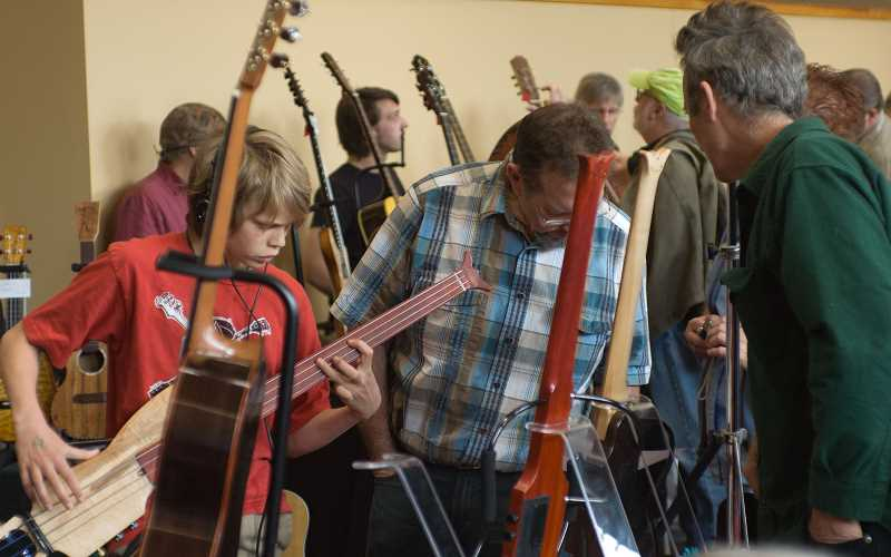 by: SUBMITTED PHOTO - Attendees view fretless guitars at the Northwest Handmade Musical Instrument Exhibit.
