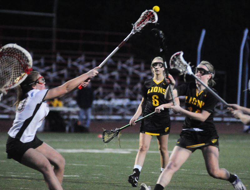 by: MATTHEW SHERMAN - West Linn's Annie Longtain tosses in one of her three first-half goals in the Lions' 11-6 victory over Oregon City which propelled the team into a tie for first place in the league.