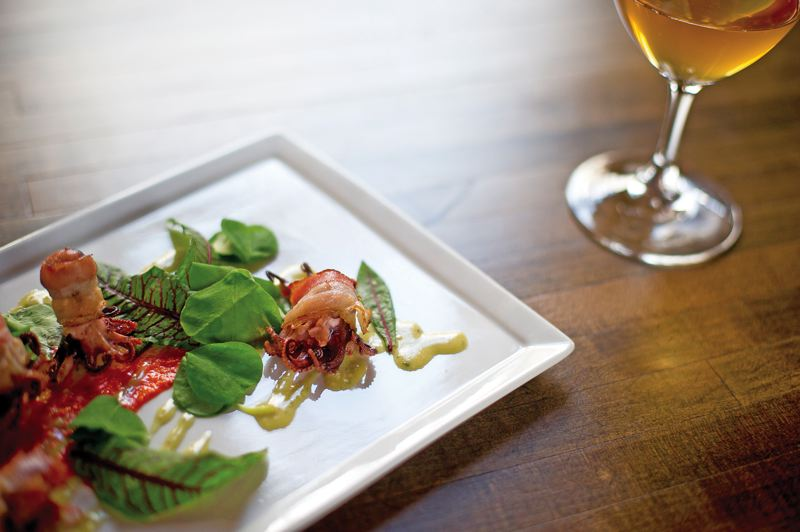 by: TRIBUNE PHOTO: CHRISTOPHER ONSOTT - The Bacon Wrapped Octopus, with Romesco and Pine Nut Ranch, alongside an Italian orange wine, is part of the enjoyment at Sauvage.