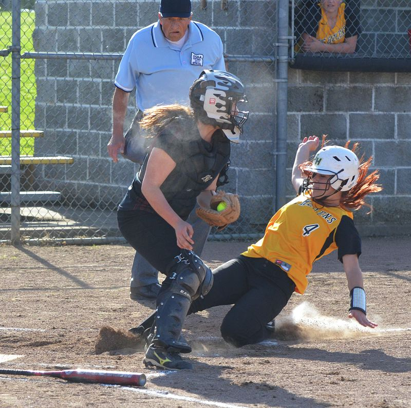 by: JOHN BREWINGTON - St. Helens' Ashley Giesbers slips home, beating a tag, for the Lady Lions second run of the first inning. St. Helens would beat Sherwood, 4-1, and stay in the thick of the NWOC race.