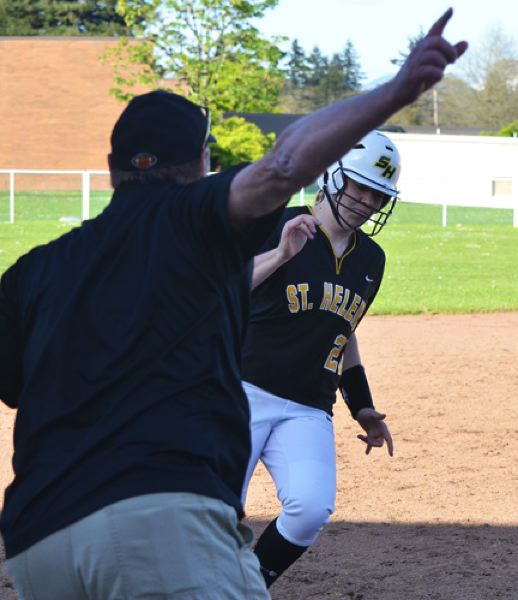 by: JOHN BREWINGTON - St. Helens softball coach Jeff Edwards sends Kali Moore home during Tuesday's game with Parkrose.