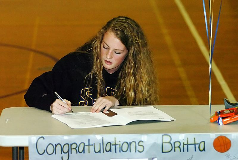 by: DAN BROOD - ON THE DOTTED LINE -- Tualatin senior Britta Hall signs her national letter of intent to play college basketball at San Jose State University.