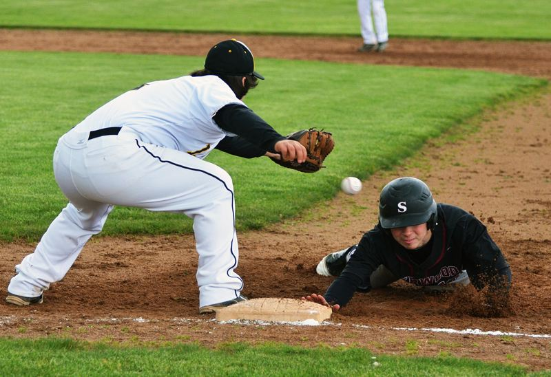 by: JOHN BREWINGTON - BACK TO THE BAG -- Sherwood senior Anthony Sherwood (right) dives back to first base during last week's game at St. Helens.
