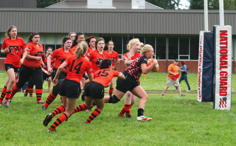 by: SUBMITTED PHOTO: RUTH MCCABE - The Crusaders' Angela VanHoomissen takes the whole Linn Benton team with her for a try during Saturday's match.