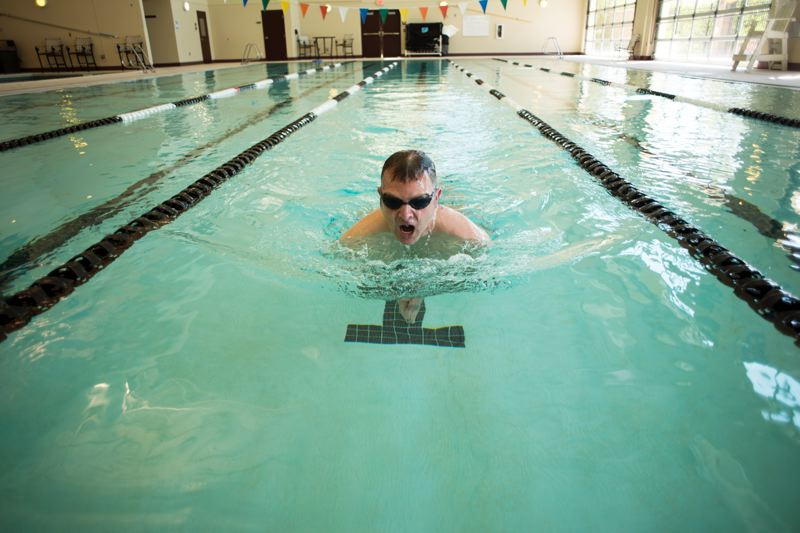 by: HILLSBORO TRIBUNE PHOTO: CHASE ALLGOOD - Richard Goerling does his morning laps Monday at Hawthorn Farm Athletic Club. It's one way Goerling, who´s bringing a new resilience training course to the Hillsboro Police Department stays in shape physically and mentally.
