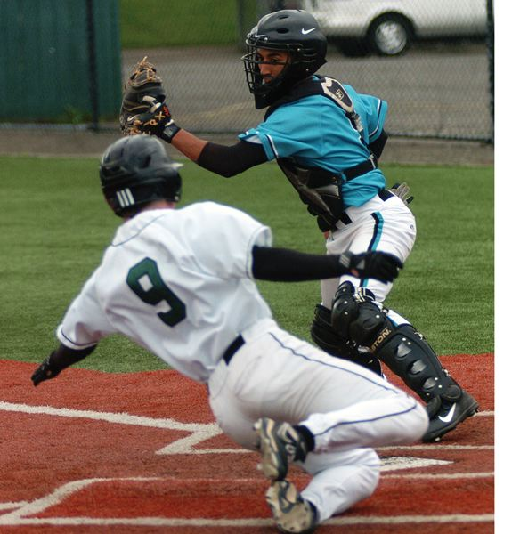 by: PAMPLIN MEDIA GROUP PHOTO: DAN BROOD - Century catcher Marcos Hernandez looks to put a tag on Tigard senior Parker Garland during last Friday's Pacific Conference baseball game.