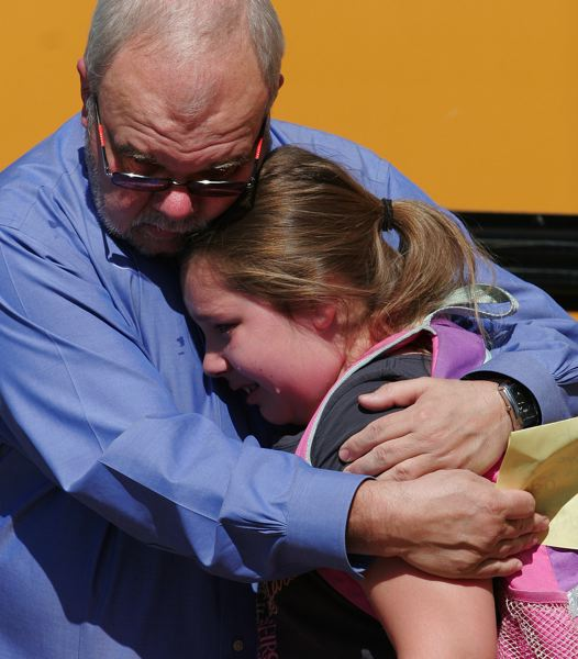 by: OUTLOOK PHOTO: JIM CLARK  - North Gresham Elementary School Principal Tom Klansnic gets a tearful goodbye hug from fourth grade student Seryna Graham at the close of school on Wednesday.