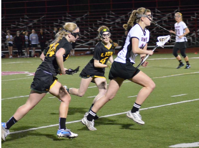 by: RAFAEL GONZALEZ - Oregon City senior captain Emily Krupa is trailed by Annie Longtain (14) and Hanna Morford (4) as she gets out on the fast break in last weeks game with top-ranked West Linn. The Pioneers dug themselves an early hole and lost the game, 11-6.