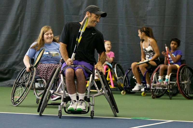 by: TIMES PHOTO: JAIME VALDEZ - Ruthanna Bedlion of Estacada chases paralympian David Wagner during a drill at the Tennis Camp for Kids.