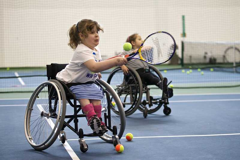 by: TIMES PHOTO: JAIME VALDEZ - Elizabeth Keen, 6, of Beaverton tries to hit a tennis ball during the Northwest Wheelchair Tennis Association Wheelchair Tennis Camps for Kids.