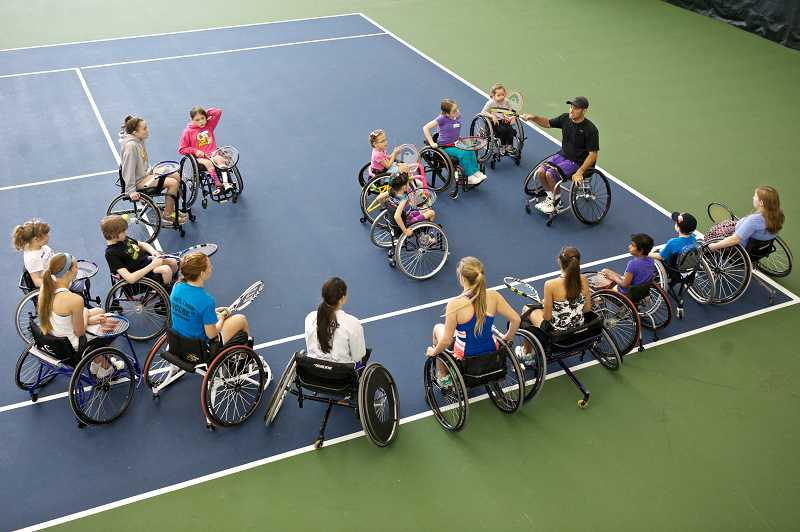 by: TIMES PHOTO: JAIME VALDEZ - Paralympian David Wagner lays out a plan for the participants of the Northwest Wheelchair Tennis Association Wheelchair Tennis Camps for Kids at the Tualatin Hills Tennis Center.