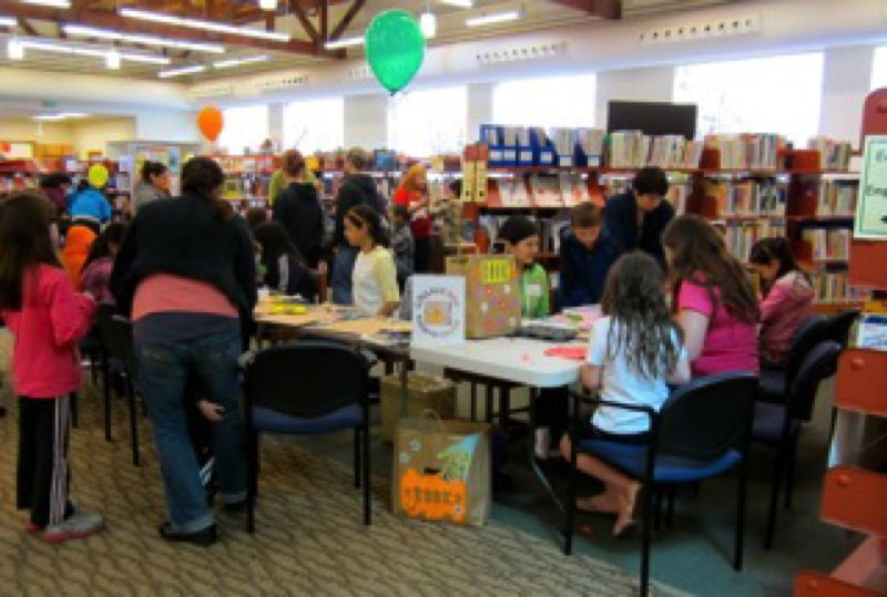 by: SUBMITTED PHOTO - Children work on crafts at last years Dia de los Ninos/Book Day celebration at the Forest Grove City Library.