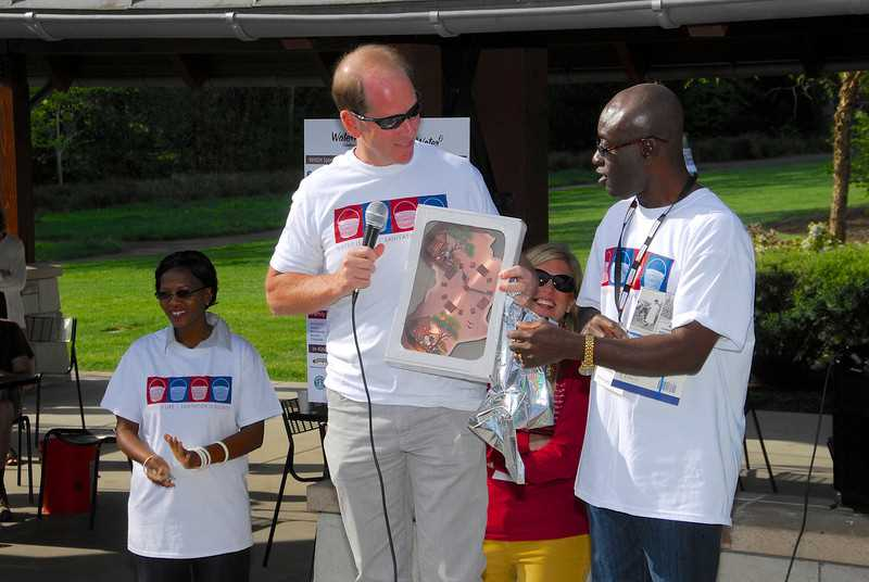 by: KEVIN CUMMINGS - Mike Kehoe, president of the Lake Oswego City Council, accepts a gift from Dr. Emmanuel Opong of World Vision. Hundreds turned out on a bright, sunny day to support Walk4Water6.
