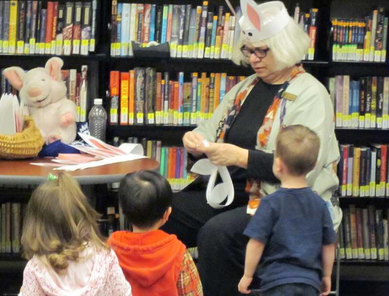 by: SUBMITTED PHOTO - Ellen Credle, known for her multisensory activities with children during story times, helps the kids with bunny ears after an Easter-themed story time in 2011.