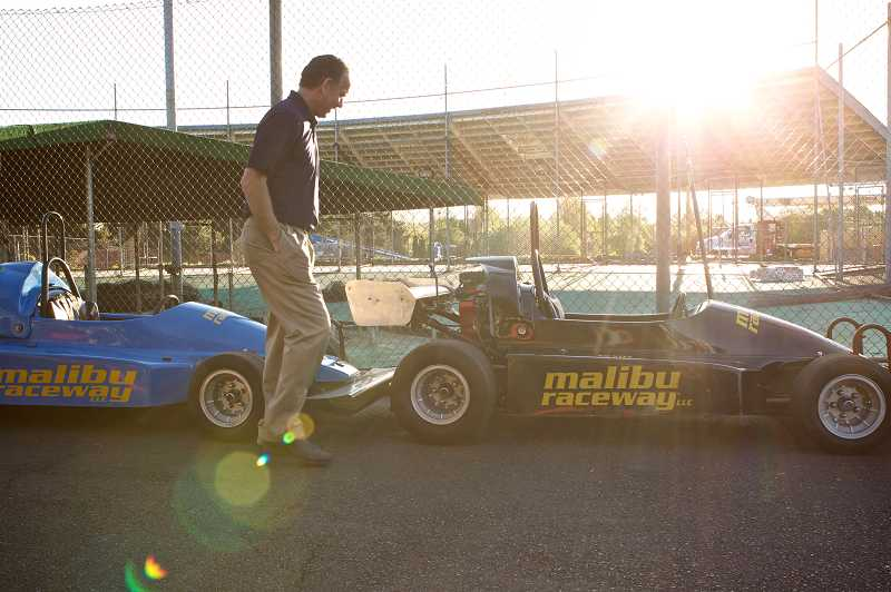 by: TIMES PHOTO: JAIME VALDEZ - Malibu Raceway Owner Kevin O'Connell walks by a row of race cars waiting to be loaded up and taken to a new location at Mt. Hood Adventure Park at Skibowl in Government Camp.