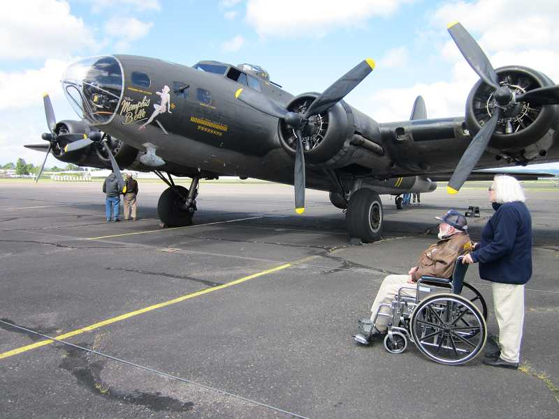by: TIMES PHOTO: BARBARA SHERMAN - Chuck Gallagher and his wife Marilyn of Beaverton look at the B-17 Flying Fortress Memphis Belle at the Hillsboro Airport before taking a flight on Monday.