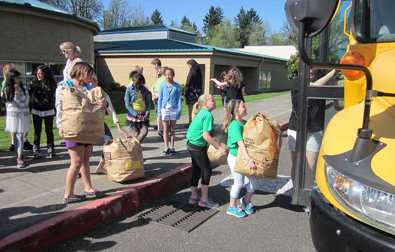 by: TIMES PHOTO: BARBARA SHERMAN - Students load hundreds of pounds of clothing into a school bus at Deer Creek Elementary School on Friday. The donations go to the Caring Closet, which distributes clothes and other items to needy students in the Tigard-Tualatin School District