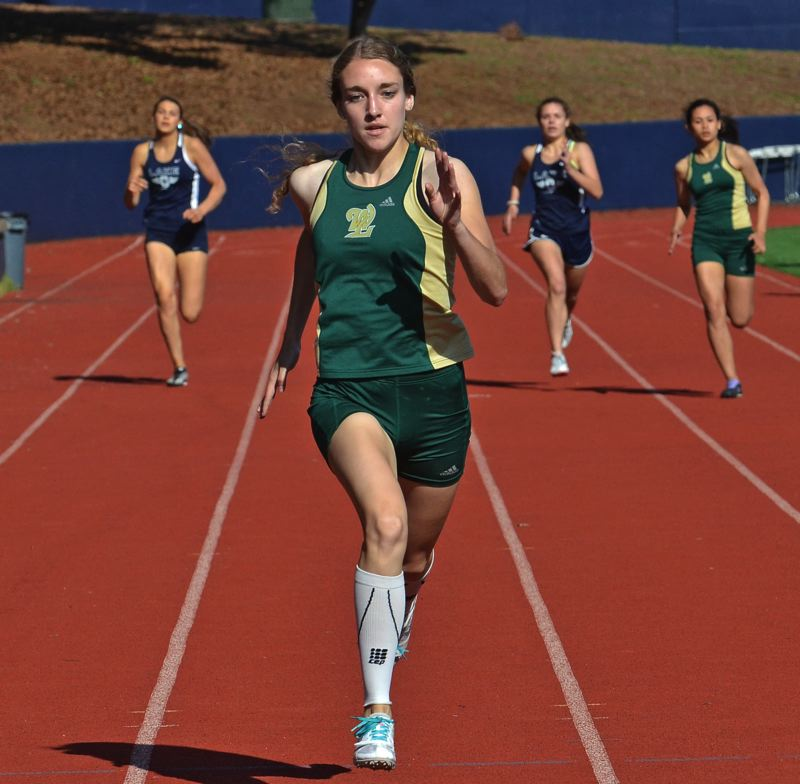 by: VERN UYETAKE - West Linn's Cara Boucher sprints to victory in the 400. Boucher also won the 200 in last week's dual meet with Lake Oswego.
