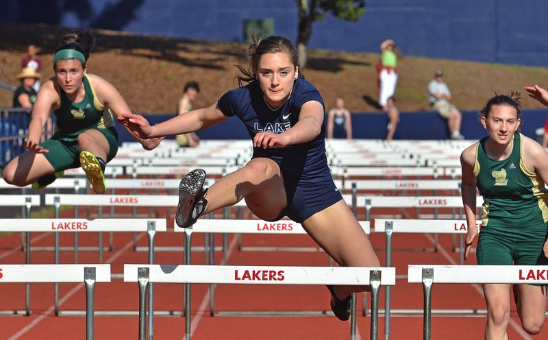 by: VERN UYETAKE - Lake Oswego's Mitra LeBuhn clears a hurdle in route to winning the 110 hurdles in last week's dual meet with West Linn.