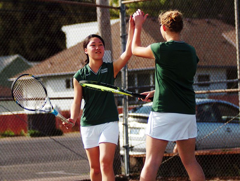by: DAN BROOD - DYNAMIC DUO -- Tigard sophomore Ayumi Mizano (left) and junior Courtney Roshak celebrate after scoring a point in their win over Hillsboro last week.