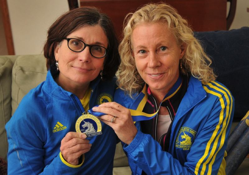by: CONNECTION PHOTO: VERN UYETAKE - Sue Strater (right) shares her medal with Claire Carder, who was kept from completing the Boston Marathon after two bombs detonated at the finish line.