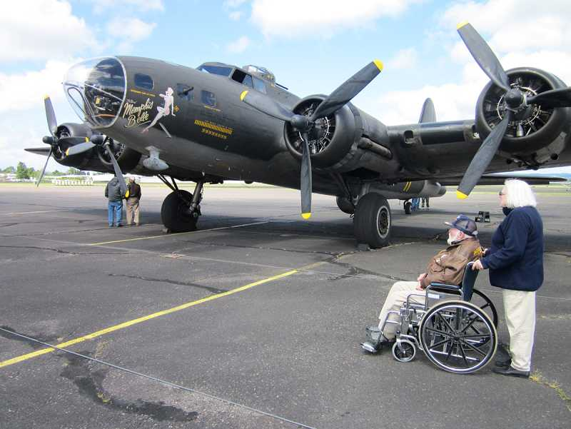 by: BARBARA SHERMAN - A SIGHT FROM HIS PAST -- Chuck Gallagher and his wife Marilyn of Beaverton look at the B-17 Flying Fortress 'Memphis Belle' at the Hillsboro Airport before taking a flight April 29.