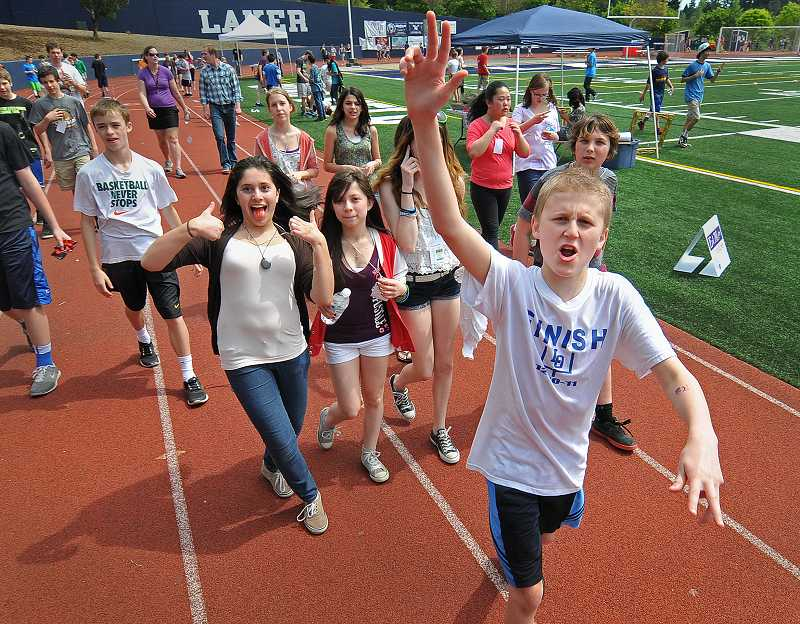 by: REVIEW PHOTO: VERN UYETAKE - Daniel Watson, front, seventh grade, leads a group of enthusiastic walkers during last Friday's Mini Relay for Life event.